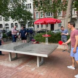 Zwei Personen spielen Tischtennis an einer Outdoor-Platte