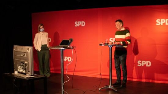 Zwei Personen stehen auf einer Bühne - hinter ihnen ein rotes SPD-Banner - vor ihnen ein Monitor und ein Tisch mit Laptop
