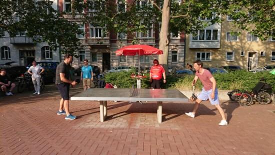 Zwei Personen spielen Tischtennis auf einer Outdoor-Platte