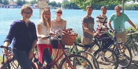 Drei Frauen und drei Männer stehen mit Fahrrädern am Ufer vom Maschsee